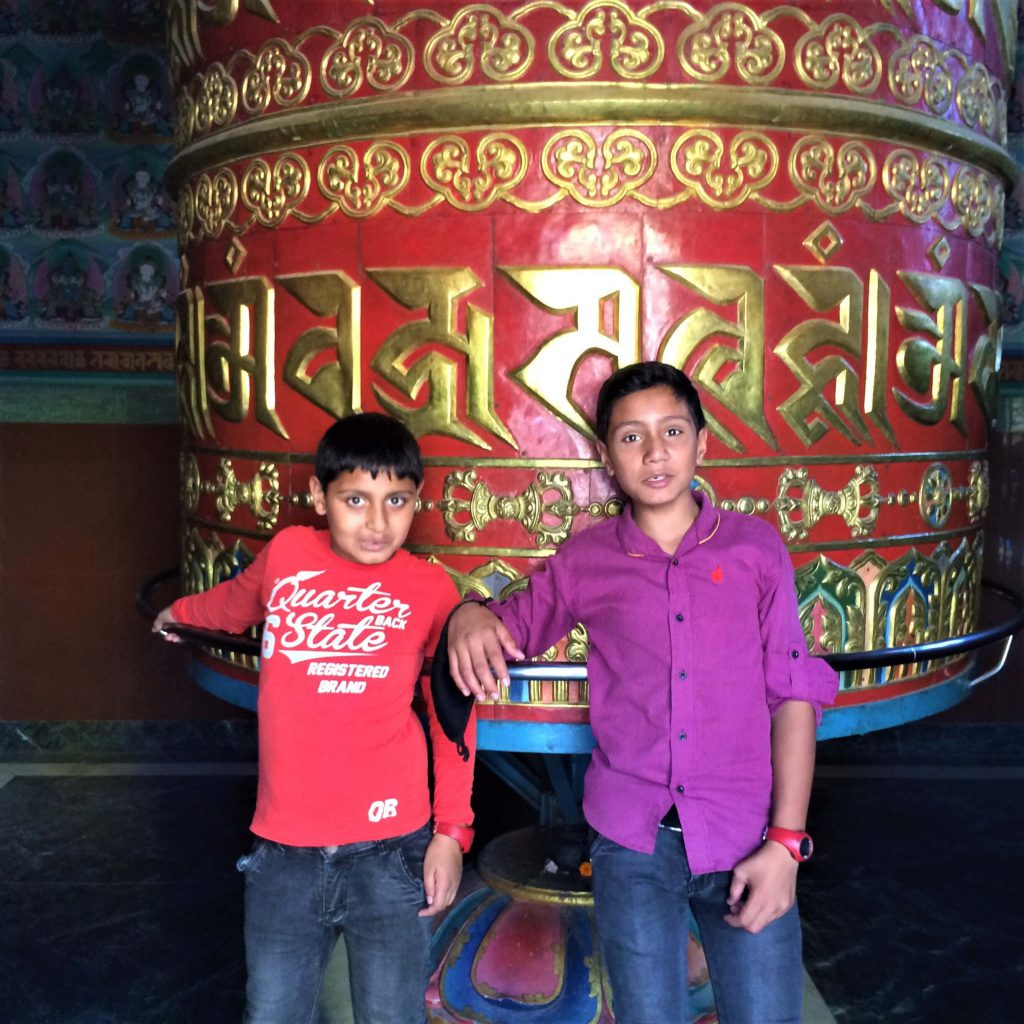Swayambunath – twee Nepalese jongens voor een grote gebedsmolen