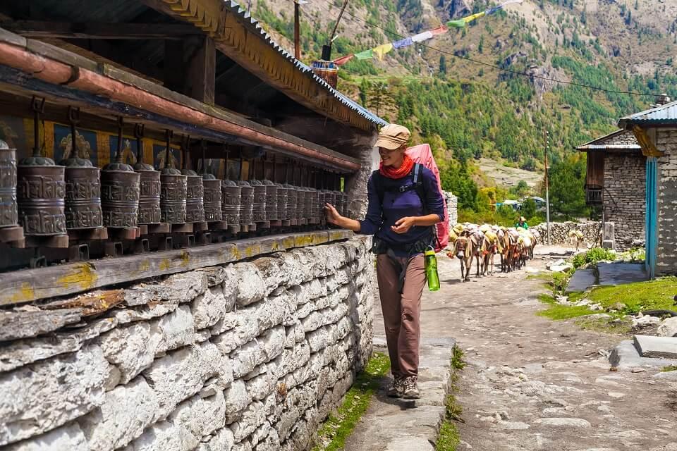 Annapurna Community trek – vrouwelijke wandelaar draait aan gebedsmolens langs de trails