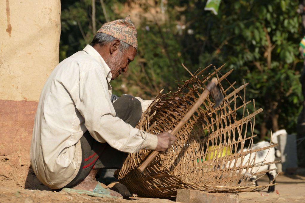 Kathmandu vallei trekking – Nepalese man met typisch Nepalees hoedje maakt een rieten mand