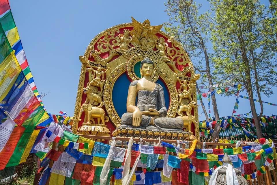 Namobuddha – beeld van Boeddha met gebedsvlagjes op het kloosterdomein