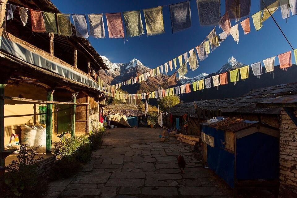Poon Hill & Muldai Peak trekking – gebedsvlagjes in het dorp Ghandruk met zicht op de Himalayas