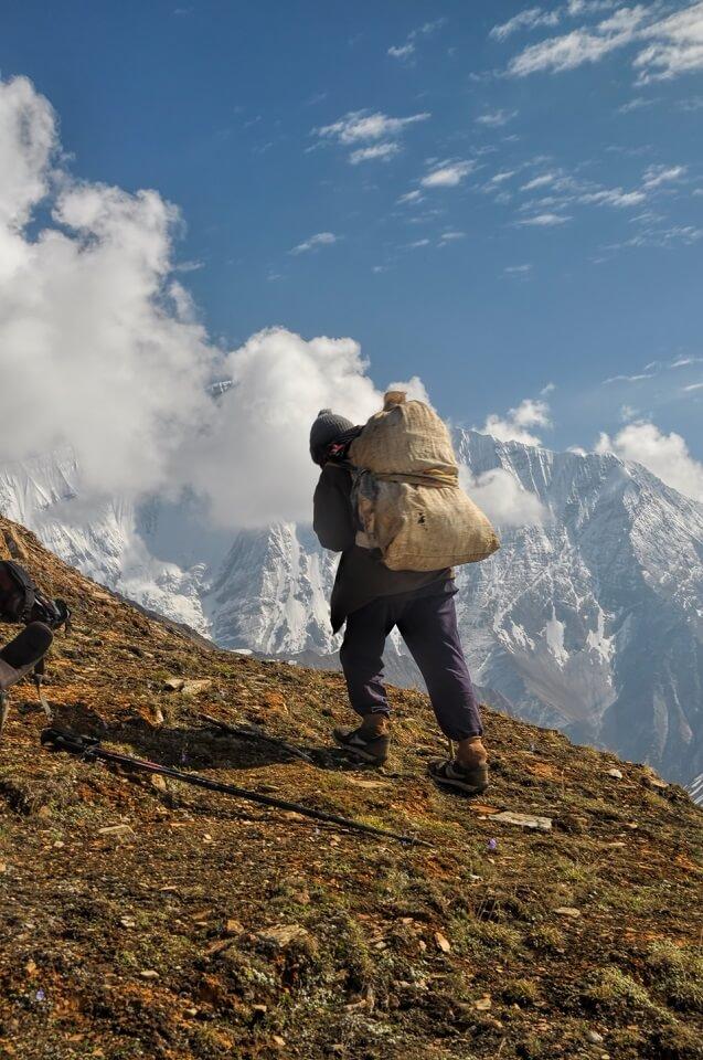 Sherpa Culture trekking – een drager draagt goederen de berg op tijdens de trekking