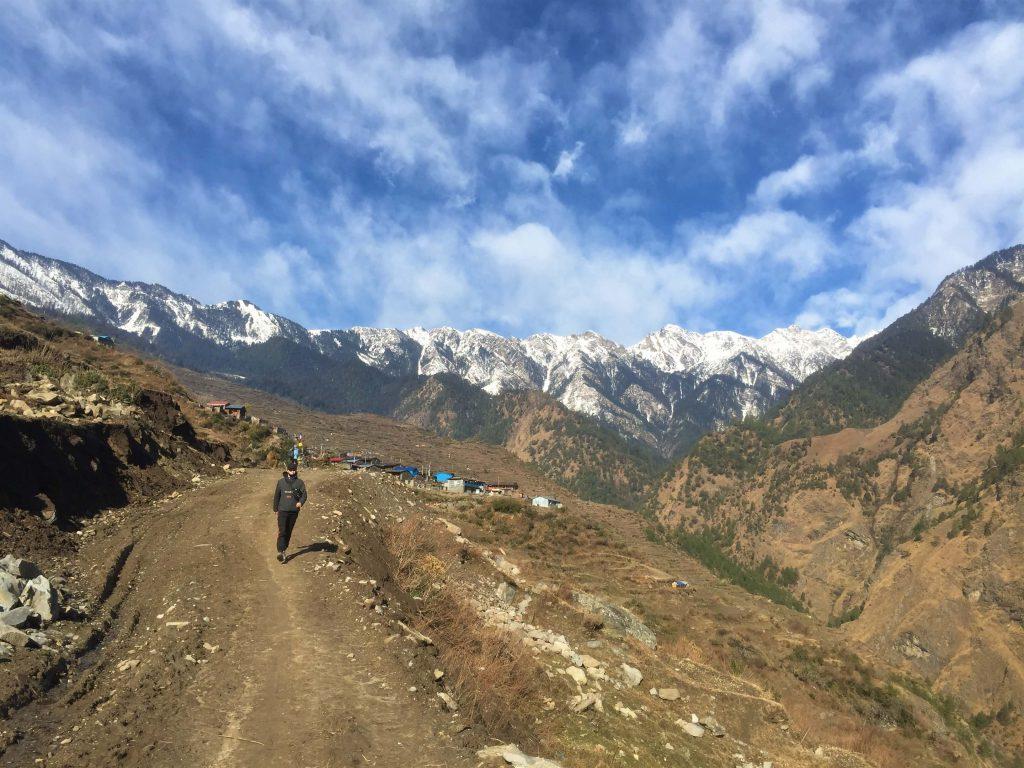 Tamang Heritage trekking – trekker wandelt weg van een dorp met zicht op de Himalayas